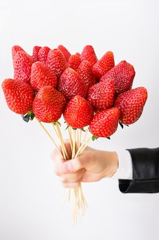 Un ramo comestible de bayas en la mano de una mujer. fresas en brochetas de madera.