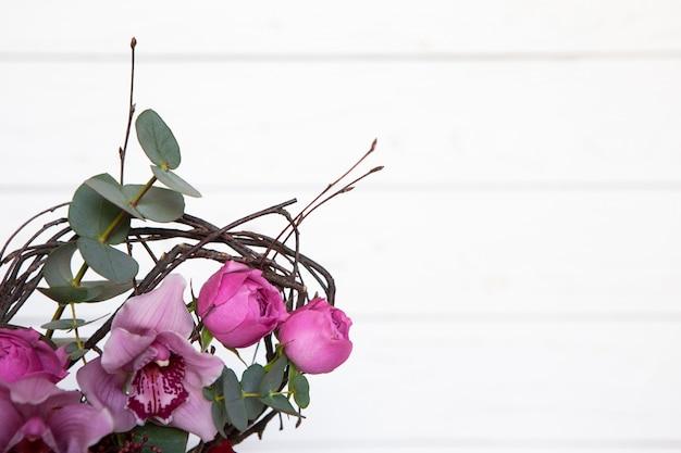 Ramo creativo de la flor en el fondo de madera blanco. centrarse en las flores, el fondo es borroso