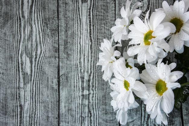 Un ramo de crisantemos blancos en gotas de agua de cerca sobre un fondo de madera