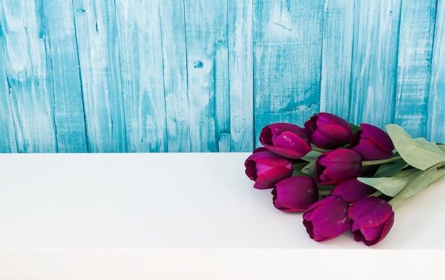 Ramo fino de la primavera de tulipanes púrpuras en la pared de madera.