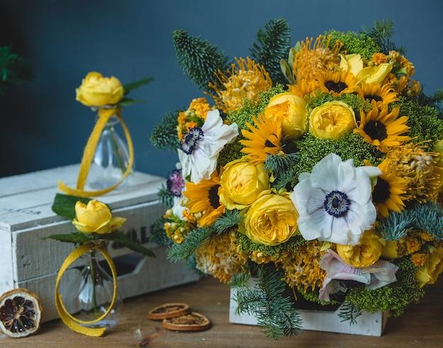 Ramo de flores amarillas blancas y pequeños jarrones de matraces alrededor