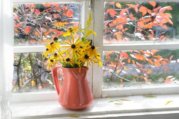 Ramo de flores amarillas en florero sobre alféizar