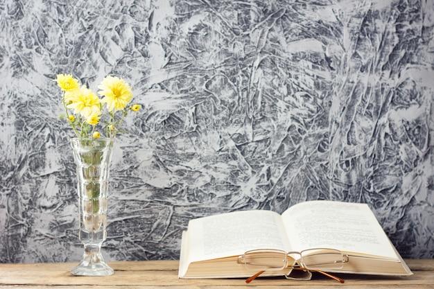 Ramo de flores amarillas con un libro sobre un hermoso fondo de madera con una copia del espacio