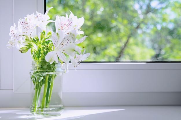 Un ramo de flores blancas alstroemeria se alza sobre un alféizar blanco bajo los rayos del sol.