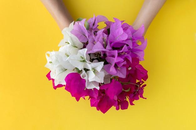 Ramo con flores blancas y rosadas en manos de mujer sobre fondo amarillo