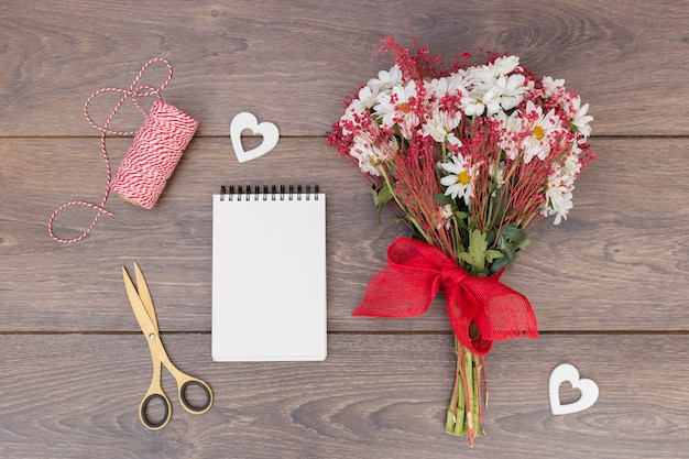 Ramo de flores con bloc de notas y corazones en mesa