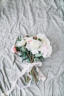 Ramo de flores de boda nupcial con peonías blancas con cinta sobre lino gris