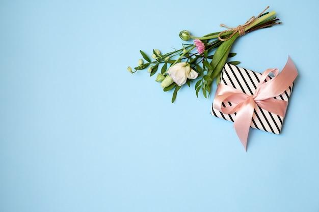 Ramo de flores, caja de regalo, cinta sobre fondo azul con espacio de copia