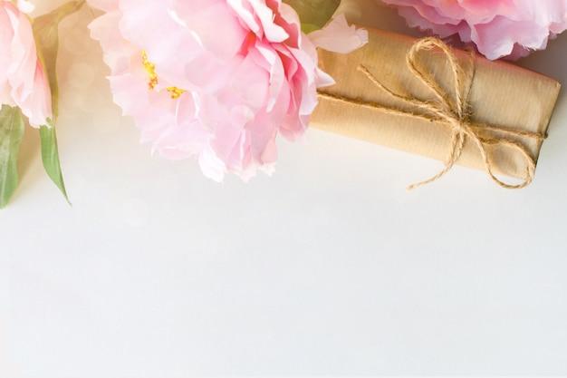 Ramo de flores y caja de regalo envuelto con papel artesanal.