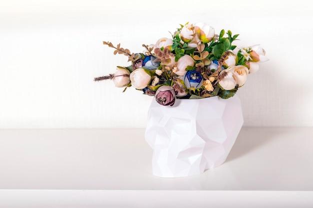 Ramo de flores en calavera de polietileno baja sobre fondo claro. decoración del hogar en estilo minimalista vanitas. concepto creativo para la fiesta de halloween.