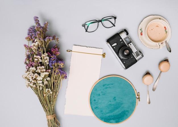 Ramo de flores con camara y cafe en mesa de luz.