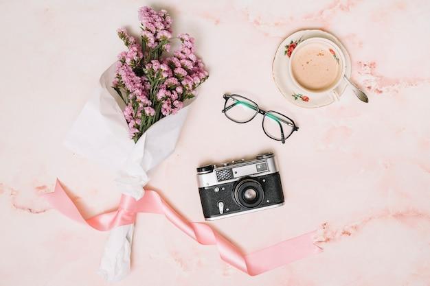 Ramo de flores con camara y cafe en mesa.