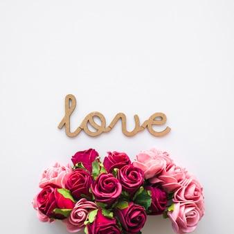 Ramo de flores cerca de la escritura amor