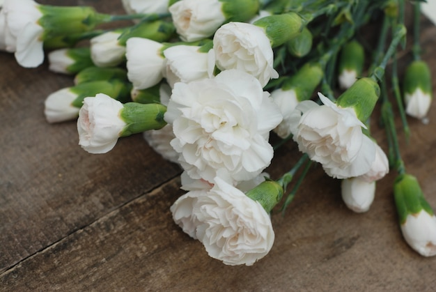 Ramo de flores de clavel blanco. madera rústica aislada.