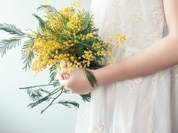 Ramo de flores de color amarillo brillante en las manos de una mujer joven con un vestido blanco