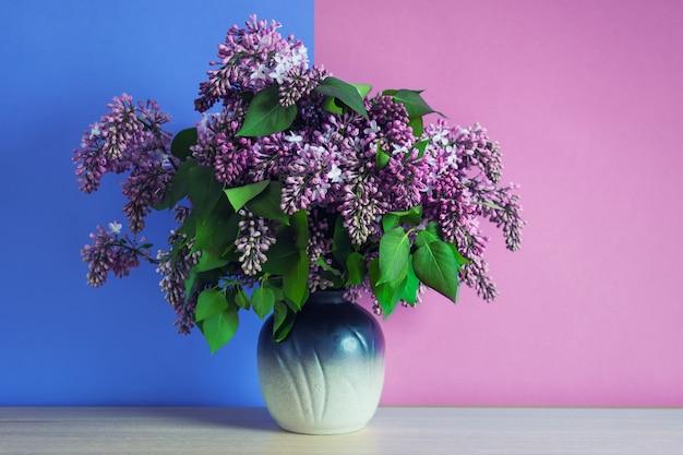 Ramo de flores de color rosa lila en un jarrón sobre fondo rosa y azul