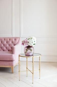 Ramo de flores de colores hortensias en florero de vidrio vintage en mesa en sala blanca. inicio acogedor interior.