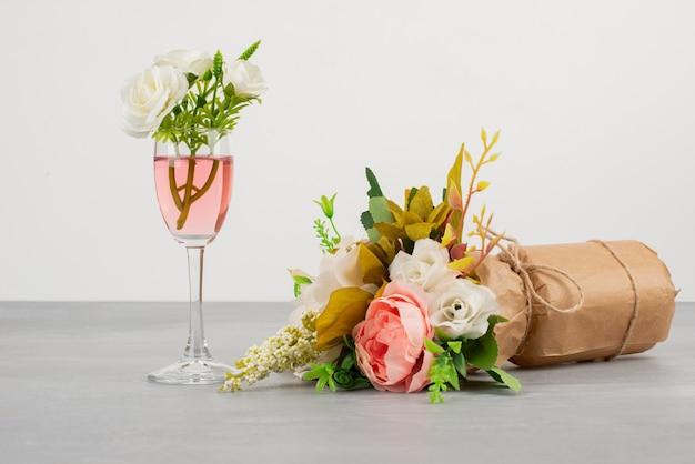 Ramo de flores y una copa de vino rosado sobre superficie gris.
