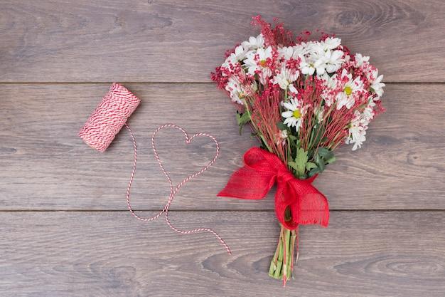 Ramo de flores con el corazón de la cuerda en la mesa