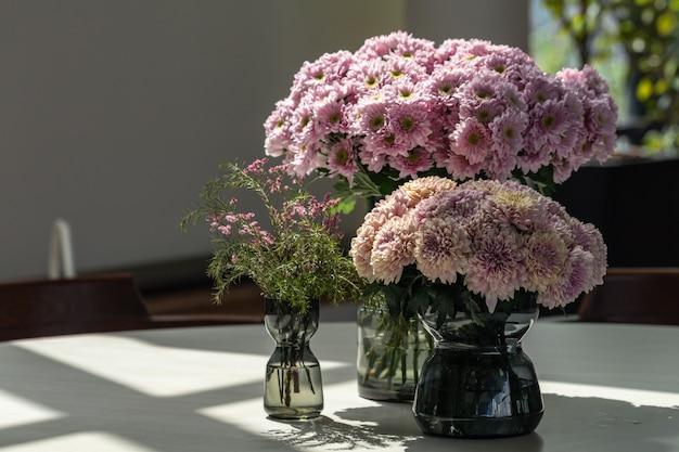 Ramo de flores de crisantemo rosa hermosa borrosa en florero de vidrio sobre la mesa.