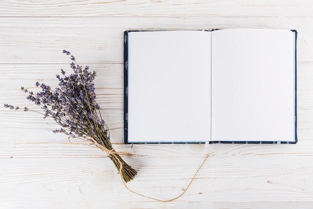 Ramo de flores con cuaderno en blanco en mesa de luz