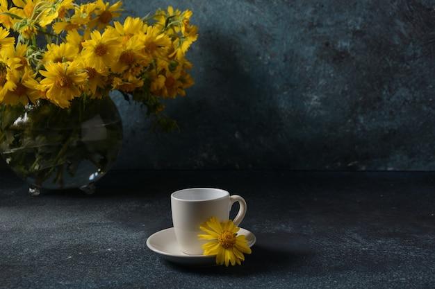 Ramo de flores doronicum y taza de café. concepto de verano