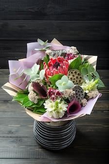 Un ramo de flores en un fondo de madera oscuro. ramillete con protea, orquídea, amapola, suculenta.
