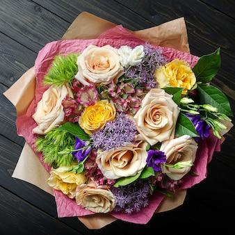 Un ramo de flores en un fondo de madera oscuro. ramo de rosas.