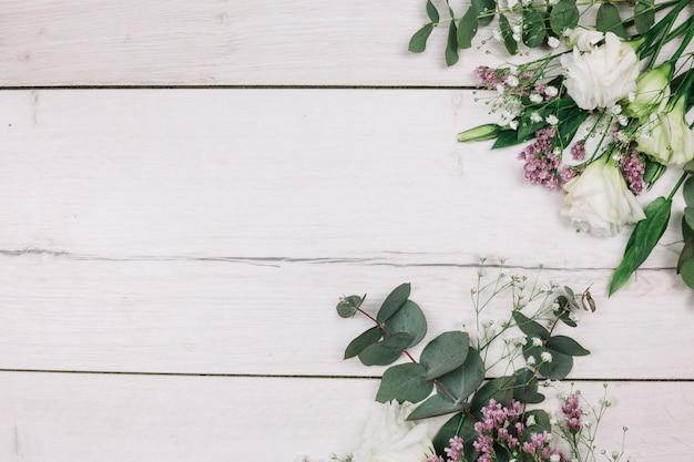 Ramo de flores frescas en el escritorio de madera blanca