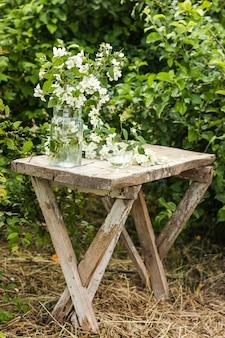 Ramo de flores frescas de jazmín fragante en un jarrón de vidrio de estilo rústico sobre una mesa de madera antigua