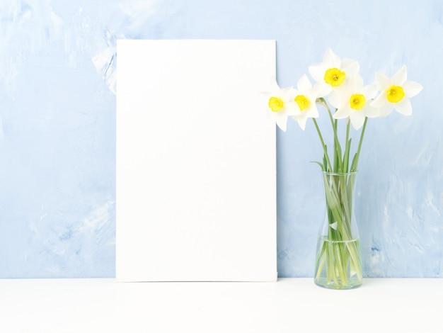 Ramo de flores frescas, papel en blanco, narcisos con un jarrón de vidrio sobre una mesa blanca
