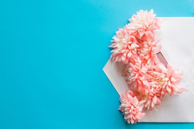 Ramo de flores frescas en sobre en azul pastel