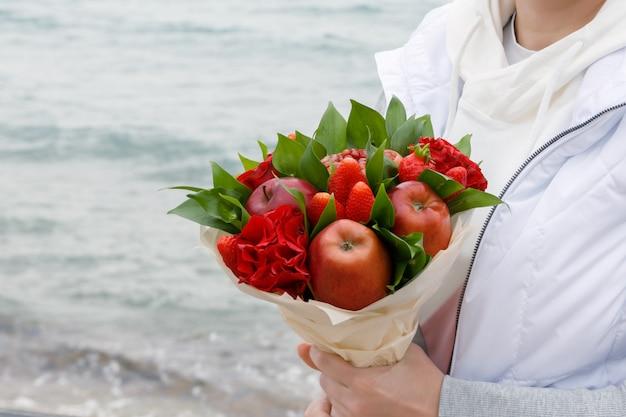 Ramo de flores y frutas en manos de una mujer.