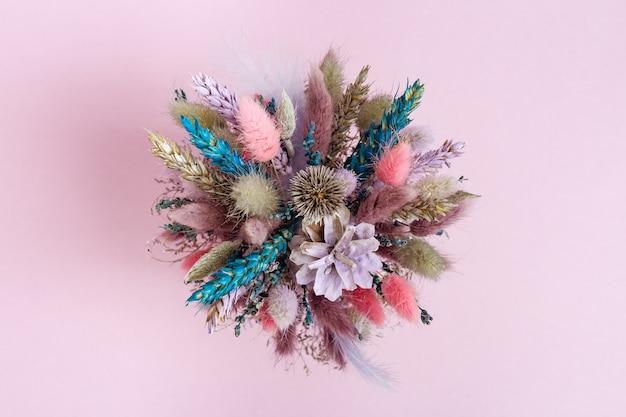 Ramo de flores hermosas y rosadas y de color lila con plantas secas, flores, hierba. decoración floral hecha a mano. vista superior.