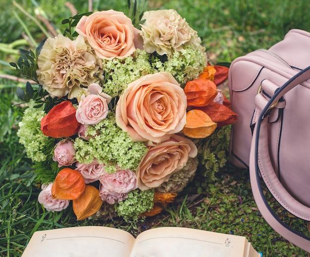 Ramo de flores en la hierba, bolso y un libro
