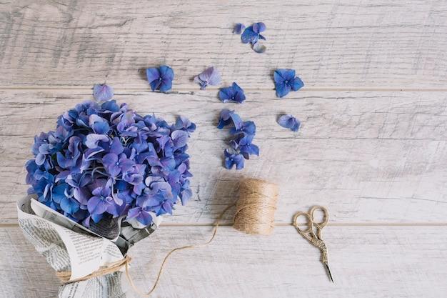 Ramo de flores de hortensia púrpura envuelto en periódico con tijera en mesa de madera