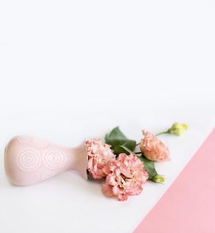 Ramo de flores en un jarrón sobre un fondo rosa