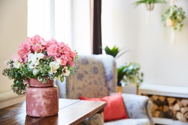 Un ramo de flores en un jarrón sobre la mesa en la sala. estilo lamentable