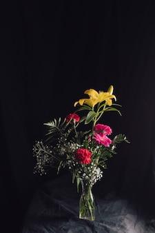 Ramo de flores en jarrón sobre textil oscuro.