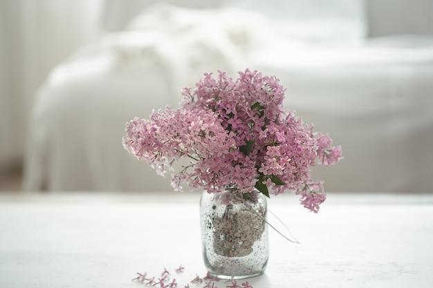 Ramo de flores lilas frescas en un espacio de copia de jarrón de vidrio.