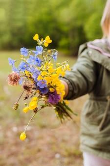 Ramo de flores en manos de una persona desenfocada