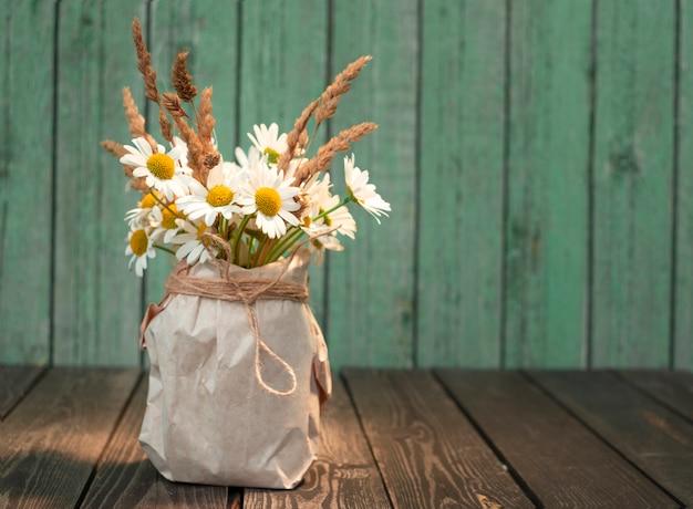 Ramo de flores de manzanilla blanca con espigas secas en un jarrón de papel kraft sobre un fondo de madera en mal estado en un estilo rústico