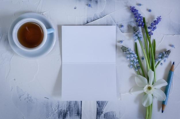 Ramo de flores de muscari con tarjeta blanca para masaje y taza de té