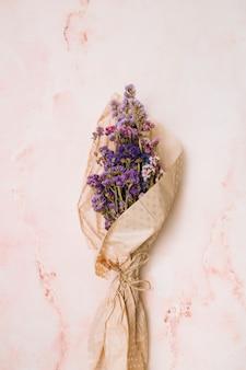 Ramo de flores en papel paquete sobre mesa de marmol.