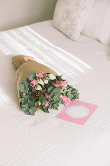 Ramo de flores en papel de regalo en la cama.