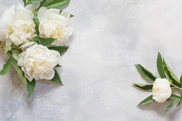 Ramo de flores de peonía blanca en mesa vintage.