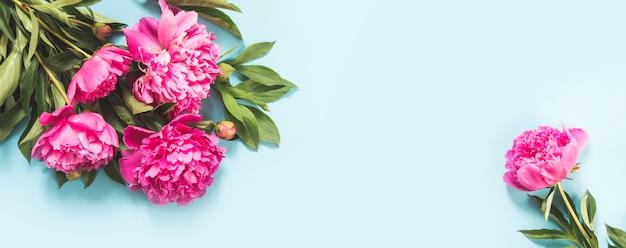 Ramo de flores de peonía rosa como marco en azul pastel. copia espacio espacio para texto.