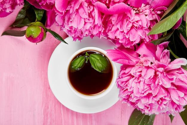 Ramo de flores de peonía y taza de café