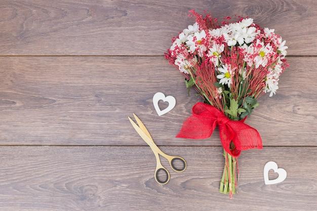 Ramo de flores con pequeños corazones en mesa.