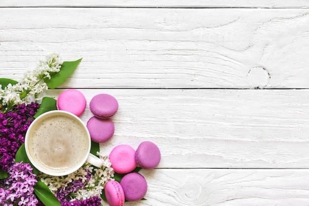 Ramo de flores de primavera lila con macarons y taza de capuchino en mesa de madera blanca